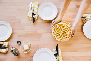 Overhead view of woman holding waffles in plate at tableの写真素材 [FYI03711285]