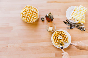 Overhead view of woman eating waffle at tableの写真素材 [FYI03711286]
