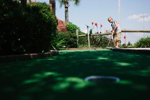 Boy playing miniature golf against skyの写真素材 [FYI03711359]