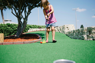 Girl playing miniature golf during sunny dayの写真素材 [FYI03711364]
