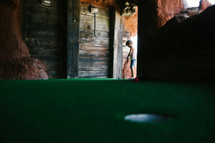 Surface level of girl playing miniature golf at doorwayの写真素材 [FYI03711365]