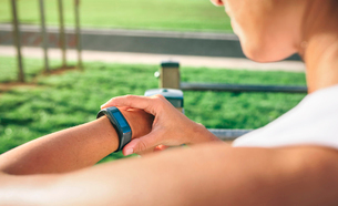 Cropped image of woman looking at smart watch while exercising at parkの写真素材 [FYI03711850]