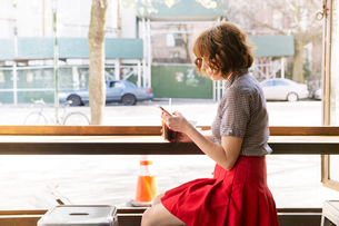 Side view of woman using smart phone while sitting against window in cafeの写真素材 [FYI03712502]