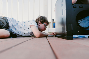 Surface level of boy using screw driver while making metallic cabinet on porchの写真素材 [FYI03712833]