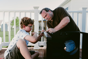 Father and son using screw driver while making metallic cabinet on porchの写真素材 [FYI03712834]