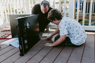 Father and son making metallic cabinet on porchの写真素材 [FYI03712836]