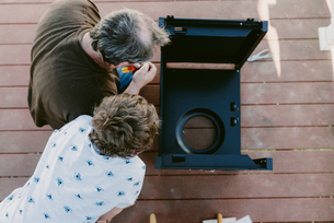 Overhead view of father and son making metallic cabinet on floorboard at porchの写真素材 [FYI03712838]