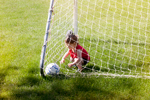High angle view of girl playing with soccer ball while crouching in goal post on grassy fieldの写真素材 [FYI03712883]