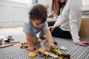 Baby boy playing with miniature train by mother on rug at homeの写真素材 [FYI03713016]