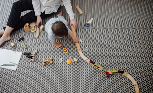 high angle view of mother and baby boy playing with miniature train on rug at homeの写真素材 [FYI03713017]