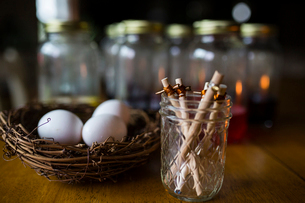 Sticks in jar by eggs on wooden tableの写真素材 [FYI03713733]