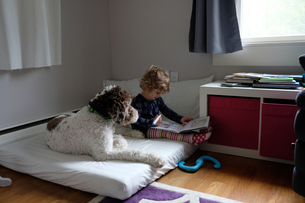 Girl studying while sitting by dog on mattress at homeの写真素材 [FYI03713752]