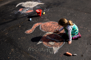 High angle view of girl drawing with chalk on asphaltの写真素材 [FYI03713753]