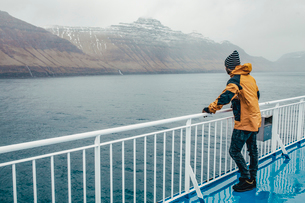 Side view of man standing by railing on boat during rainy seasonの写真素材 [FYI03713978]