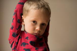 Portrait of boy with hands behind head against beige backgroundの写真素材 [FYI03713983]