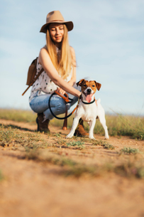 Woman petting dog while crouching at field against skyの写真素材 [FYI03714061]