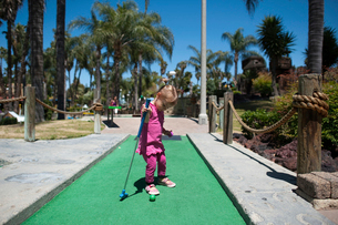 Full length of girl playing miniature golf on sunny dayの写真素材 [FYI03714097]