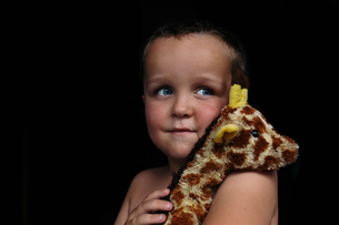 Thoughtful shirtless boy looking away while holding toy against black backgroundの写真素材 [FYI03714138]