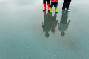 Low section of friends reflecting while standing on wet city street during rainy seasonの写真素材 [FYI03714205]