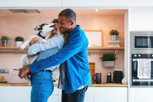 Affectionate multi-ethnic couple playing with Siberian Husky at homeの写真素材 [FYI03714298]