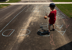 Rear view of boy playing with ball while standing on road with chalk drawingの写真素材 [FYI03714334]