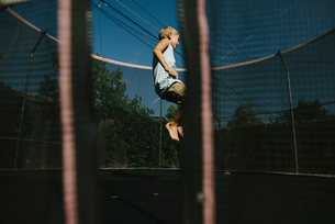 Boy jumping on trampolineの写真素材 [FYI03714356]