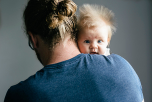 Portrait of daughter carried by father against gray backgroundの写真素材 [FYI03714410]