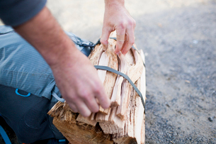 Cropped hands of hiker tying tied up firewood on bagの写真素材 [FYI03714492]