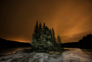 Tranquil view of trees by Two Jack Lake against cloudy sky during duskの写真素材 [FYI03714505]
