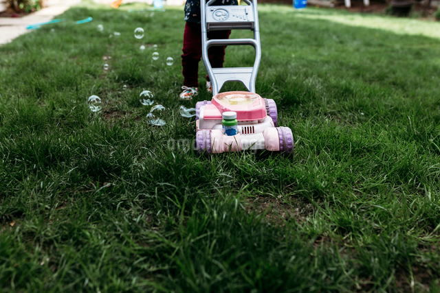 Low section of girl standing by bubble mower in lawnの写真素材 [FYI03714784]