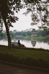 Rear view of woman looking at view while sitting on bench at Hoan Kiem Lakeの写真素材 [FYI03715084]