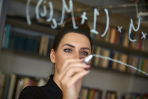 Businesswoman writing formula on glass wall at officeの写真素材 [FYI03715216]