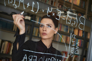 Businesswoman writing formula on glass wallの写真素材 [FYI03715219]
