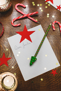 Overhead view of paper with pencil and Candy canes on table during Christmasの写真素材 [FYI03715435]