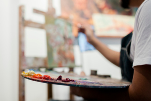 Midsection of painter holding palette while painting in studioの写真素材 [FYI03715577]