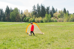 Boy playing soccer on grassy field during sunny dayの写真素材 [FYI03715808]