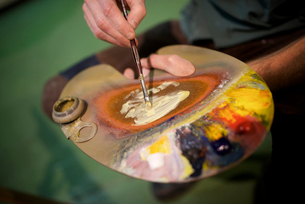 Midsection of man with watercolor paint palette in workshopの写真素材 [FYI03715915]