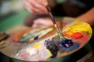 Close-up of man with watercolor paint palette in workshopの写真素材 [FYI03715916]
