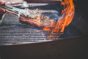 Cropped hand of man turning steak on barbequeの写真素材 [FYI03716008]