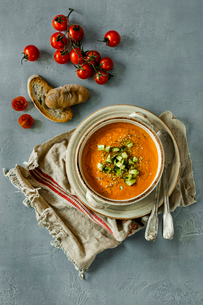 Overhead view of Gazpacho served in bowl by bread and cherry tomatoes at tableの写真素材 [FYI03716043]