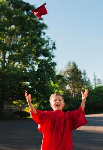 Portrait of happy boy in graduation gown throwing mortarboard on footpathの写真素材 [FYI03716178]