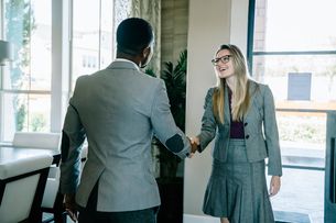 Business people shaking hands while standing against door in officeの写真素材 [FYI03716864]