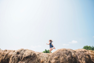 Carefree girl running on heap of hay against skyの写真素材 [FYI03717096]