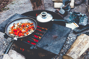 High angle view of food in cooking pan on fire pit at campsiteの写真素材 [FYI03717994]