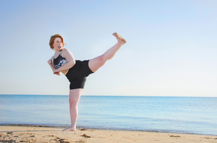 Woman practicing kickboxing at beach against clear skyの写真素材 [FYI03718249]
