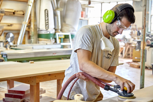 Carpenter using ear and eye protection while sanding wooden plank in workshopの写真素材 [FYI03718263]