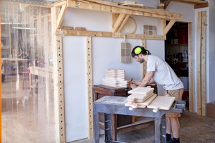 Side view of carpenter wearing ear protection while working in workshop against wallの写真素材 [FYI03718266]