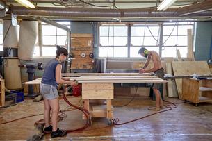 Full length of carpenters sanding wooden planks in workshopの写真素材 [FYI03718269]