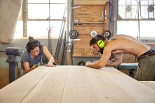 Carpenters sanding wooden planks in workshopの写真素材 [FYI03718270]