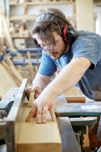 Carpenter wearing ear protection while working in carpentry workshopの写真素材 [FYI03718272]